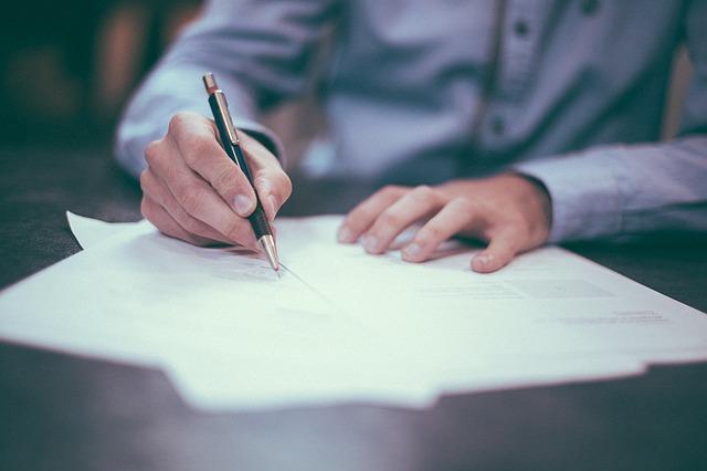 Mãos de um homem escrevendo em papeis sobre uma mesa.